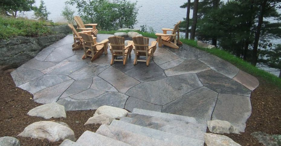 After: A nice stone patio with chairs overlooking a like