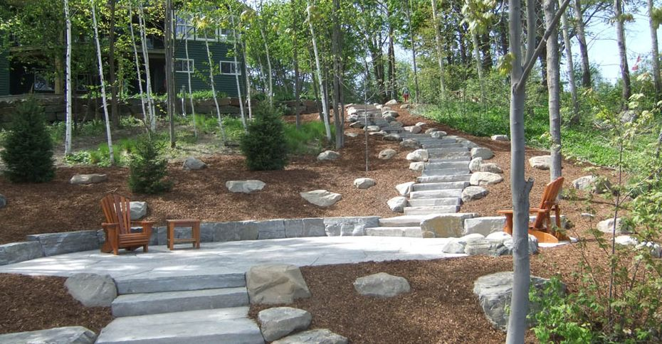 After: A landscaped hill with a patio for sitting and a stone walkway
